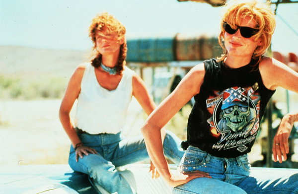 Thelma and Louise sit on top of the Thunderbird in all their bad ass glory, taunting the truck driver.