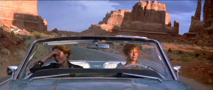 Thelma and Louise driving, top down, through the desert, rock formations behind them.